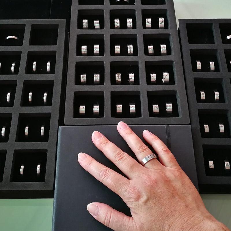Auswahl an Größenmusterringen und eine Hand mit Musterring