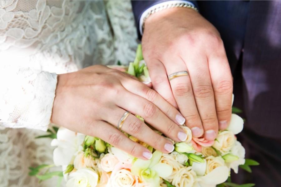 Eheringe an den Händen eines Brautpaars